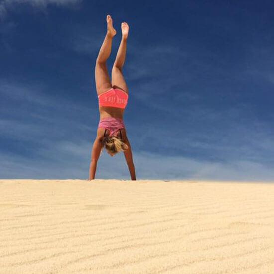 Mädchen macht Handstand im Sand
