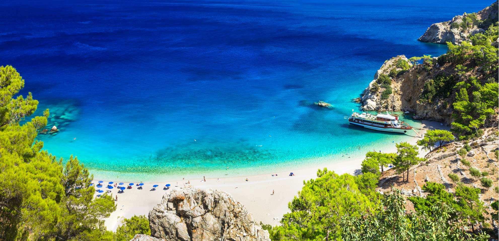 Strand auf den Kanarischen Inseln mit Felsen, Bäumen und Schiff